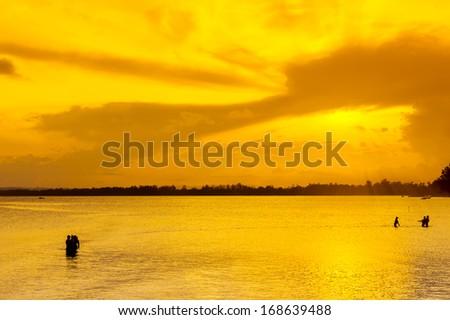 silhouette fisherman via dramatic sunset