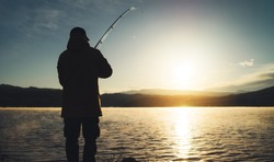 silhouette fisherman with fishing rod at sunrise sunlight, outline man enjoy hobby sport on evening lake, person catch fish at night sky, relaxation fishery concept