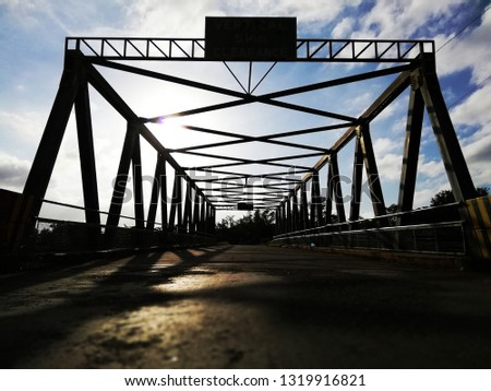 Silhouette framework of a small bridge made with steel iron metal against a bright blue sky in broad daylight