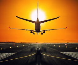 Silhouette from a landing airplane at the runway. Beautiful sunset sky. Travel and transportation concept
