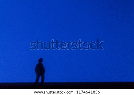 Silhouette from the shadow of a lonely dreamy man staring into the distance on a blue wall. The concept of loneliness, dreaminess and romance. #1174641856