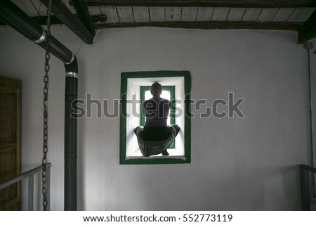 Silhouette girl on the window with white wall. #552773119