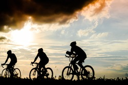 silhouette group of men ride bicycles at sunset with black cloud in background.