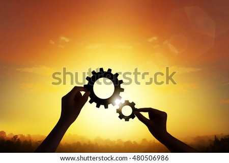 Silhouette hand holding gear mechanism sign for cooperation. teamwork concept.  cooperation concept.  lens flare.