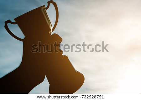 Silhouette hand holding winner trophy cup in a championship , Winner's trophy award gold with sky sunset , Cup and Champion winning concept.