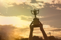 silhouette hand holding winner trophy cup in a championship with sky sunset.