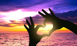Silhouette hand in heart shape on sunset over the sea