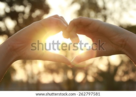 silhouette hand in heart shape with sunlight and flare  #262797581