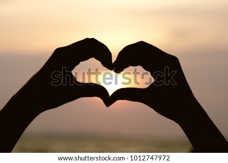 Silhouette hand in heart shape with sunrise in the middle and beach .as background Valentine concept with copy spaces for your text or design.