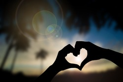 Silhouette hand in heart shape with sunset scene background