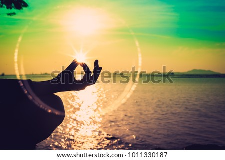 Silhouette, hand of Woman Meditating in Yoga pose or Lotus Position by the Sea at Sunset. Rear View. Nature Meditation Concept. Low key photo. relax time.