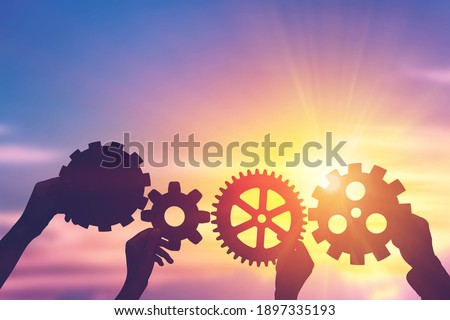 Silhouette hands holding gear from at sunlight background. concept of a teamwork cooperation idea.