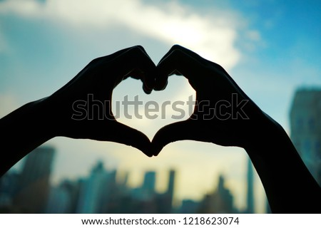 Silhouette hands making heart shaped hand gesture on blurred background of cityscape with high rise business metropolis building and skyscape with clouds at early morning or evening moment. #1218623074