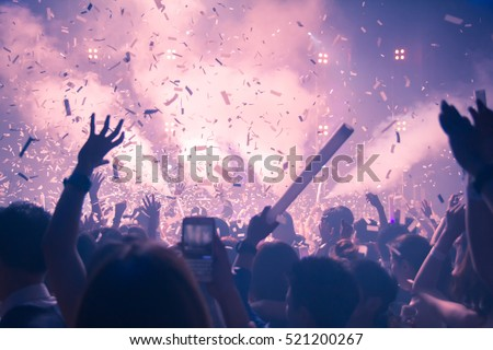 Silhouette hands of audience crowd people use smart phones enjoying the club party with concert.  Celebrate new year party , Blurry night club DJ party people enjoy of music dancing sound .