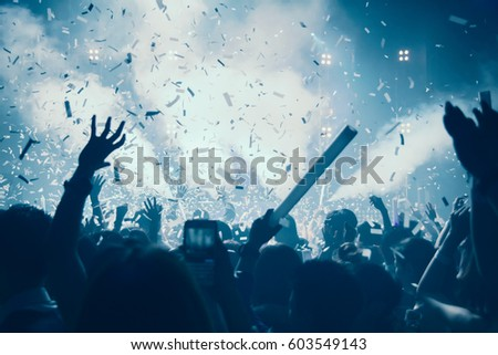 Silhouette hands of audience crowd people use smart phones enjoying the club party with concert. Celebrate new year party , Blurry  people movement  enjoy of music dancing sound .