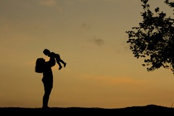 Silhouette happy mother and baby. Mother plays with her baby in her arms under the rays of the sunset in a meadow. Motherhood concept. Happiness, inspiring, joyful moments. Mother's day concept.