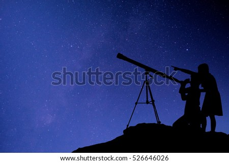 Silhouette happy time of boy and girl with telescope on the rock at the star background  #526646026