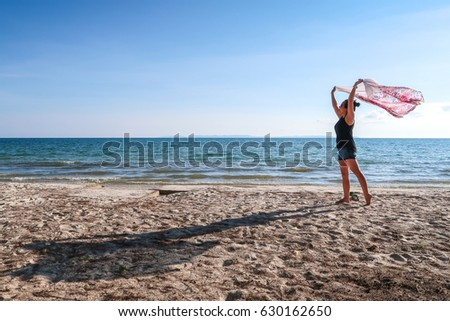 silhouette happy woman dancing at the beach blue sky  #630162650