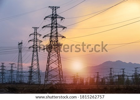 Silhouette high voltage electric pylon and electrical wire with an orange sky. Electricity poles at sunset. Power and energy concept. High voltage grid tower with wire cable at distribution station. Stockfoto ©