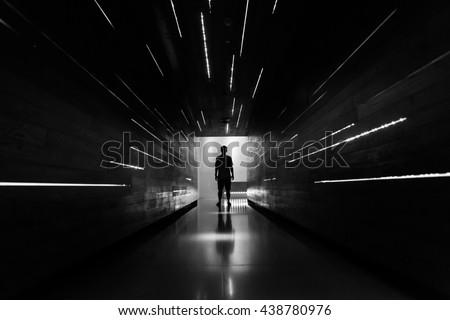 Silhouette human in the center of beautiful corridor design. #438780976