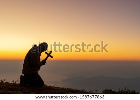 Silhouette human kneeling down praying and holding christian cross for worshipping God at sunset background.Christian, Christianity, Religion copy space background.