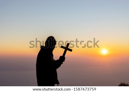 Silhouette human praying and holding christian cross for worshipping God at sunset or sunrise background.Christian, Christianity, Religion copy space background.