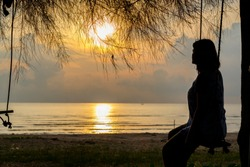 Silhouette image at beachfront. A woman looking at sunrise,sitting on the wooden swing