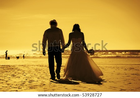 Silhouette image of a bride and groom by the beach at sunset. (toned image)