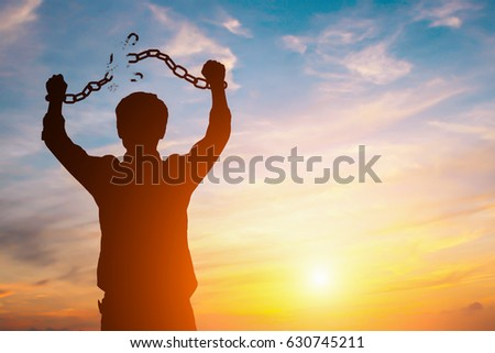 Silhouette image of a businessman with broken chains in sunset #630745211
