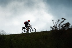 Silhouette image of a cyclist riding the Otago Central Rail Trail against the cloudy sky, South Island, New Zealand