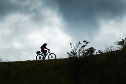 Silhouette image of a female cyclist riding the Otago Central Rail Trail against the cloudy sky, South Island, New Zealand