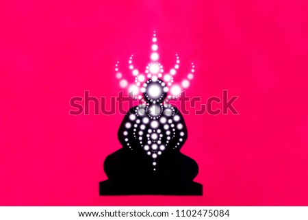 Silhouette image of a meditator in trance, light geometric patterns of prana, a person in nirvana, a buddha of enlightenment