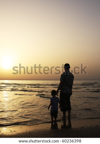 Silhouette image of father and his child by the sea shore, sunset
