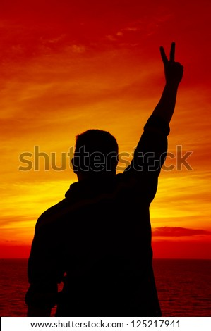 Silhouette Image of Man Raising His Hand Showing Two Fingers