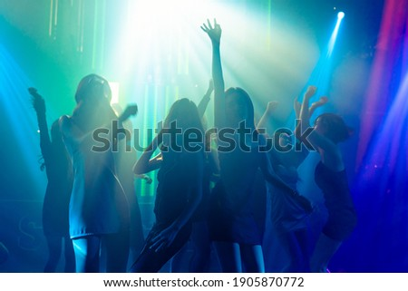 Silhouette image of people dance in disco night club to music from DJ on stage . New year night party and nightlife concept . Photo stock ©