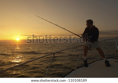Silhouette image of young man fishing on yacht