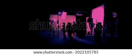 Silhouette images of film production. behind the scenes or b-roll of making video commercial movie. Film crew lightman and cameraman working together with film director in studio. Film industry.