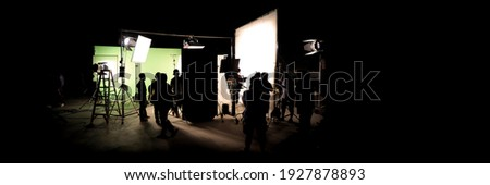Silhouette images of video production behind the scenes. making of TV commercial movie that film crew team lightman and cameraman working together with film director in studio. film production concept Stockfoto ©