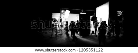 Silhouette images of video production behind the scenes or b-roll or making of TV commercial movie that film crew team lightman and cameraman working together with director in big studio  #1205351122