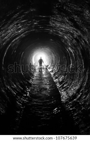 silhouette in a  communication tunnel. Light at End of Tunnel