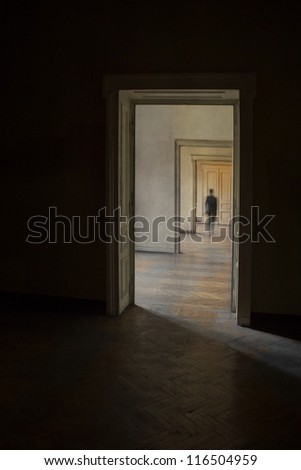 Silhouette in a corridor in front of a closed door. Rite of passage concept. Linear perspective view through several open doors and empty rooms. - stock photo