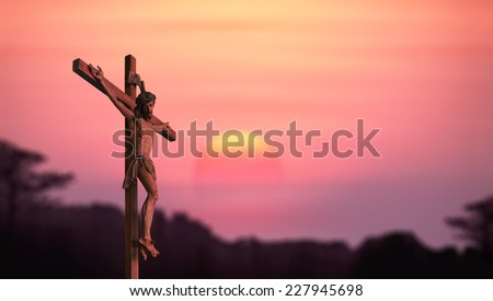 Silhouette Jesus and the cross over blurred sunset background