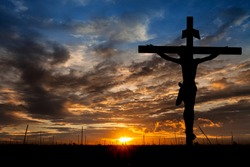 Silhouette Jesus Christ crucifixion on cross over calvary sunset background concept for he is risen in easter day, good friday jesus death on crucifix, world christian happy and holy spirit religious.