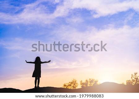 Silhouette kid pray and worship to GOD on the sunset sky.Kid child girl praying believe.Raised hands blessing worship jesus, Hope, freedom prayer.Faith,Praise, holy spirituality and religion.