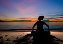 Silhouette  lady practice yoga for healthy  on the beach with twilight sky background.