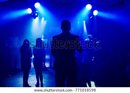 silhouette leading into nightclub scene with dancing on dance floor people at event #771018598