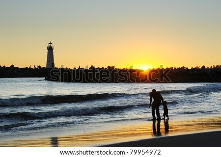 silhouette light house and father and son on the beach in summer time at sunset