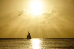 SILHOUETTE: Lonely sailboat sails across the tranquil ocean on a beautiful golden-lit summer evening. Scenic view of luxury tourist boat sailing along the picturesque calm shore of Barbados at sunset.
