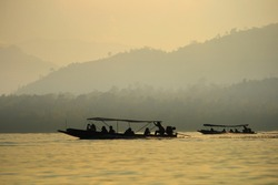 Silhouette long tail boat with passenger on board. ship adventure in to lake and river in a forest wetland. soft morning sky and mountains outlined