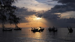 Silhouette long tail boats. ,traditional fishing boats. anchored. In the sea  background is beautiful sunset. Samui Thailand